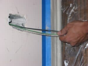 electrician pulling wires through hole in wall